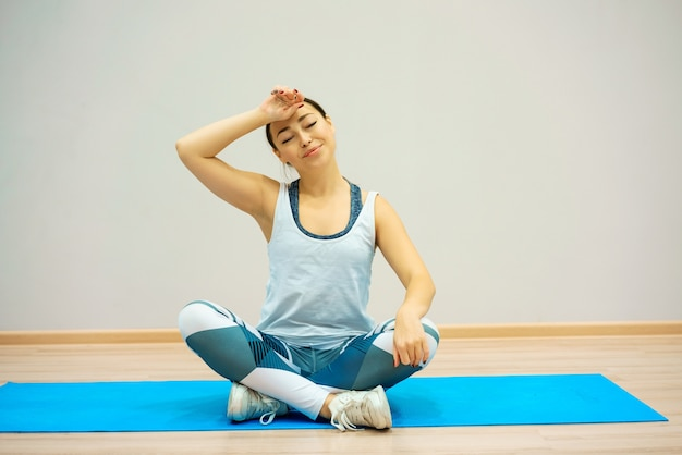 A woman sits on the mat tired after training