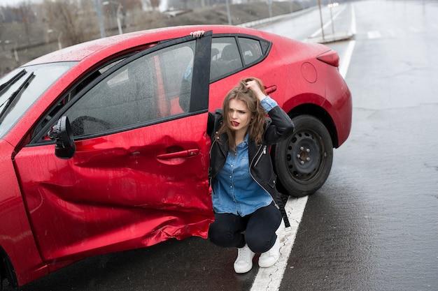 Женщина сидит возле разбитой машины после аварии. звать на помощь. страхование автомобиля