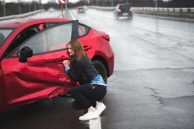 Woman sits near a broken car after an accident. call for help. car insurance