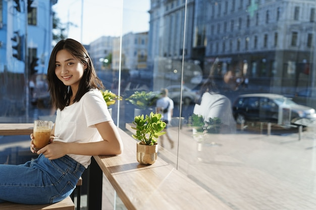 Woman sits near counter and drink coffee, behind passersby and cars on streets, smiling joyfully