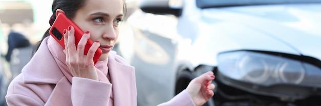 여성이 난파 된 자동차 옆에 앉아 스마트 폰 교통 사고 및 자동차 검사에 대해 이야기합니다.