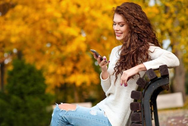 Женщина сидит на скамейке осенью в парке, держит мобильный телефон и улыбается