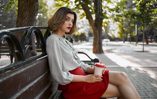 女性は自然の中で公園のベンチに座って、彼女の手で一杯のコーヒーを持っています。高品質の写真