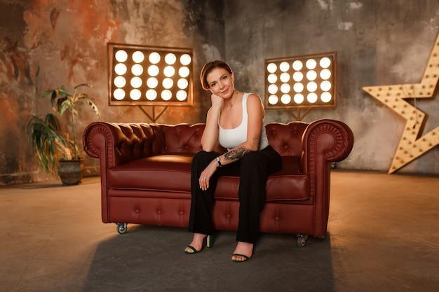 Женщина сидит на кожаном диване в выразительной позе, смотрит на камеру.