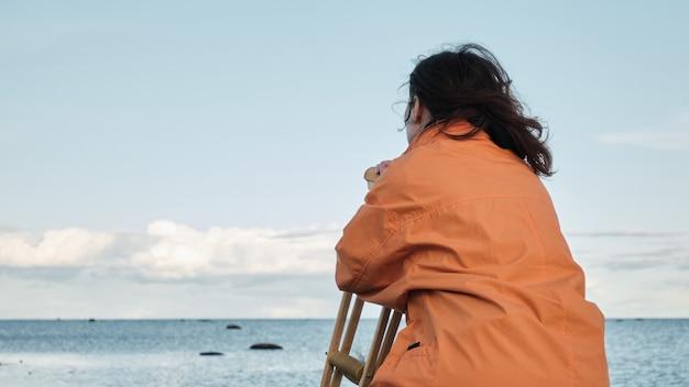 여자는 목발에 기대어 돌에 앉아서 호수를 찾습니다. 수평선에 잔잔한 호수와 구름을 배경으로 모래 해변