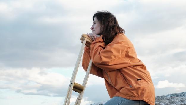 여자는 목발에 기대어 돌에 앉아 호수를 본다