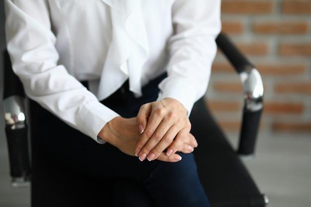 女性は握りしめられる手で椅子に座っています。