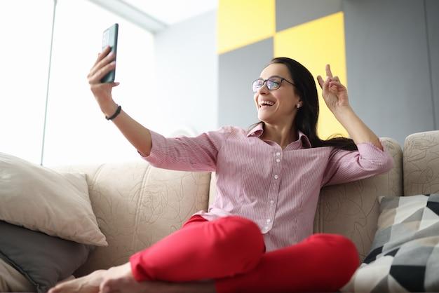 Женщина сидит на диване и, улыбаясь, здоровается с собеседником на видео трансляции