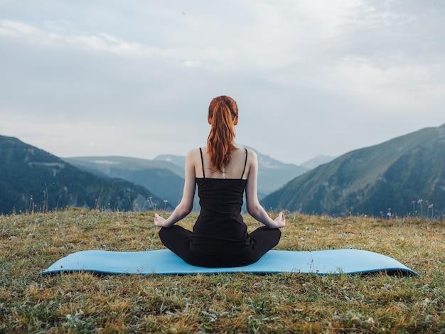 여자는 피트니스 매트에 앉아 산에서 야외 요가 아사나를 묵상합니다.