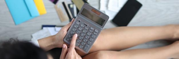 Женщина сидит на полу с калькулятором рядом с банковскими картами и счетами