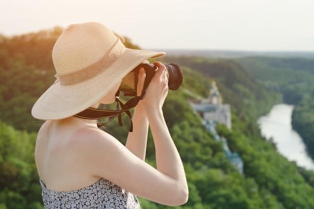 女性は丘の上に座って、森と川を背景に写真を撮ります