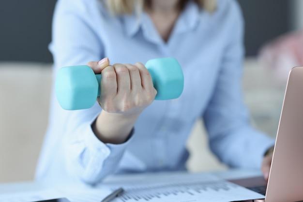 女性はラップトップに座って、彼女の手に青いダンベルを持っています
