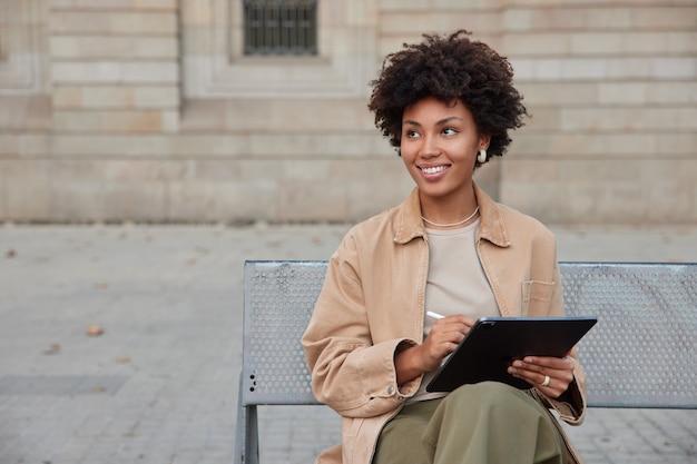 여성은 스타일러스가 있는 태블릿의 금속 벤치 스케치에 앉아 세미나를 준비하며 도시 지역 편집 프로젝트에서 최신 가제트를 사용하는 알림을 기쁘게 확인합니다