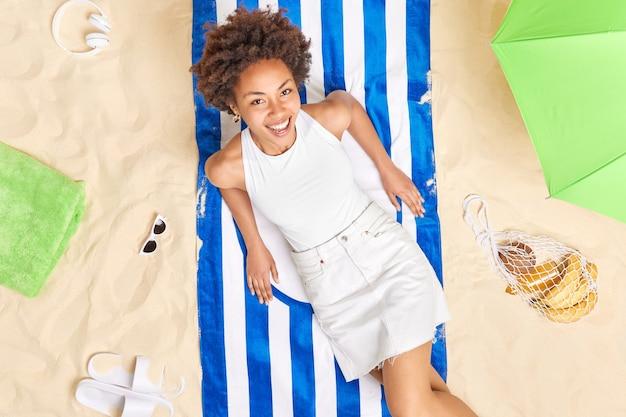 縞模様のタオルの上に座っている女性は、夏の装いを喜んで着ているように見え、夏休みをビーチの日光浴で過ごし、リラックスした気分になります。最高の休日のコンセプト。