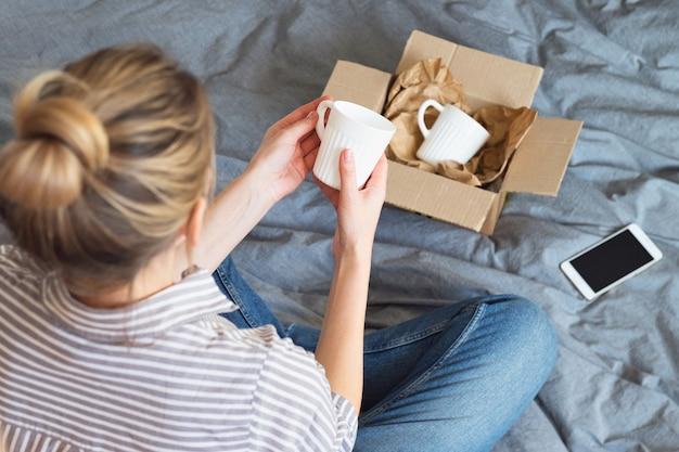 女性はベッドに座って、皿の入った段ボール箱を開梱し、オンラインで商品を購入し、配達のコンセプトを説明します。