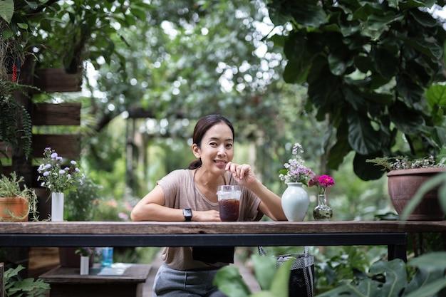 庭でアイスコーヒーを飲む木製の椅子に座っている女性