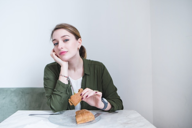 Woman sits in restaurant with light interior and dinner. girl with sandwich in her hands looks at camera.