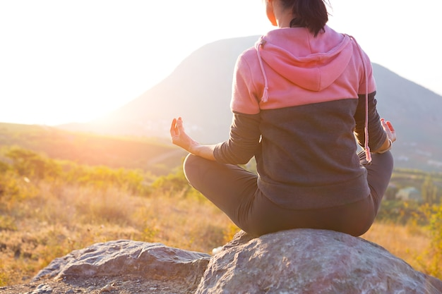 A woman sits on a rock in the lotus position