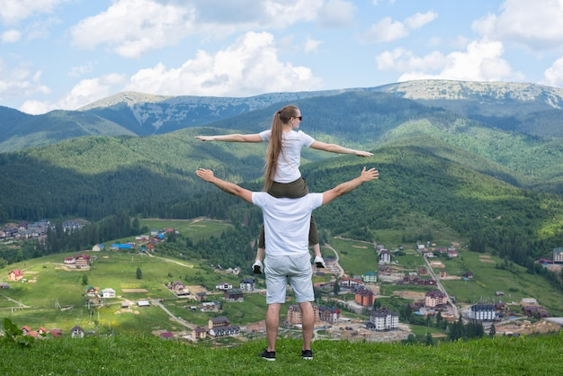 Woman sits on the shoulders of the guy and admire the mountains. back view