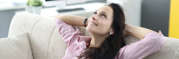 Woman sits on sofa and looks up dreamily.
