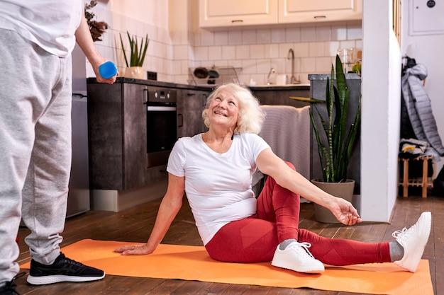 남편이 아령으로 운동하는 동안 여자는 바닥에 스트레칭 앉아, 그녀는 그를보고 미소