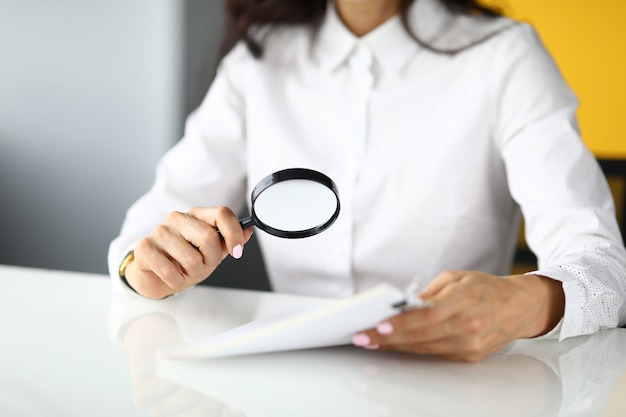 Woman sits at table and holds magnifying glass and documents in her hands.