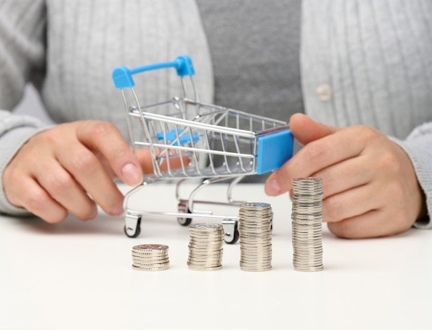 The woman sits at the table and holds a miniature cart and stacks of white coins. concept of savings, sale, tax