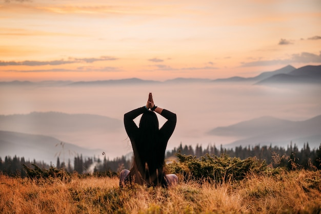 Woman sits on top of a mountain at sun rise.