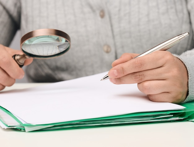 A woman sits at a white table and holds a metal pen over a pile of papers, in the other hand a magnifying glass. finding mistakes, analyzing the budget