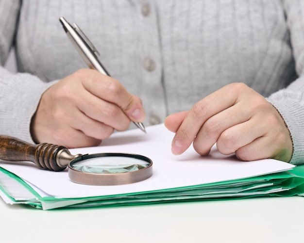 Woman sits at a white table and holds a metal pen over a pile of papers, in the other hand a magnifying glass. finding mistakes, analyzing the budget