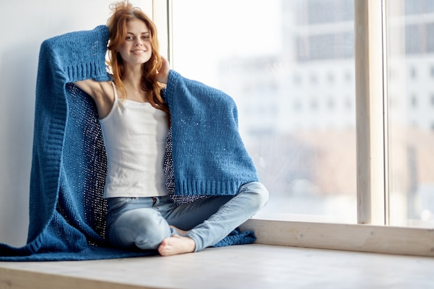 A woman sits on the windowsill covered with a blanket and looks out the window.