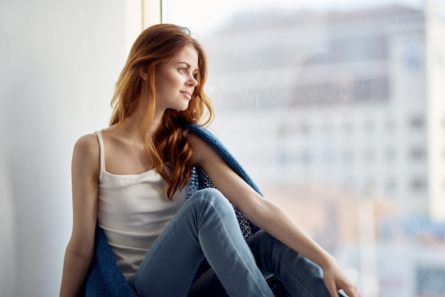 A woman sits on the windowsill covered with a blanket and looks out the window