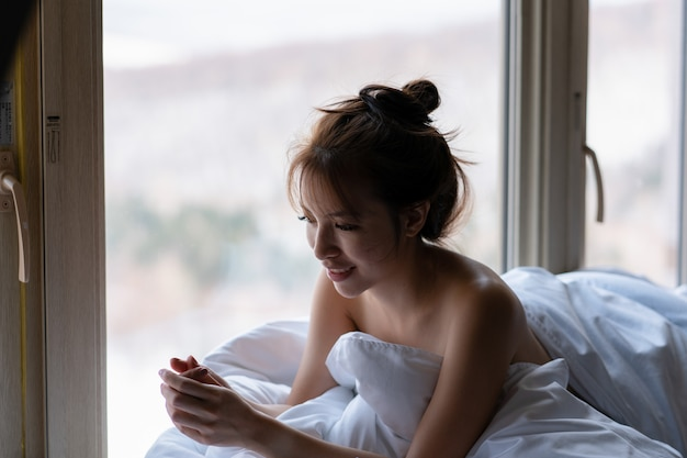Woman sits on a windowsill wrapped in a warm blanket