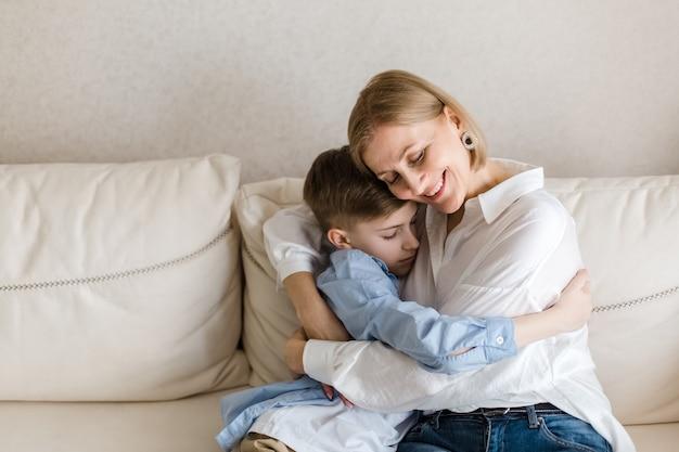 Женщина сидит с подростком, обнимая и улыбаясь