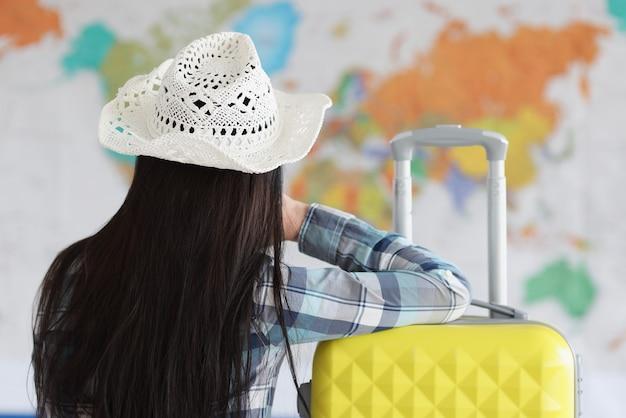 여자는 흰 모자와 가방에 등을 대고 앉아 세계지도를 본다.
