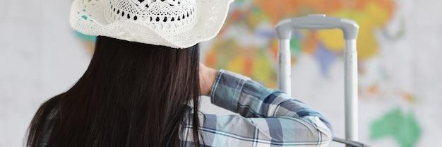 女性は白い帽子とスーツケースに背を向けて座って、世界地図を見る