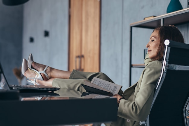 Woman sits with her feet up on her desk.