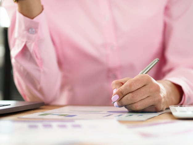 Woman sits at workplace and takes notes on chart