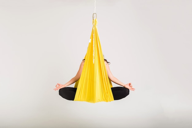 A woman sits in a yellow hammock in a namaste pose on a white isolated wall with space for text
