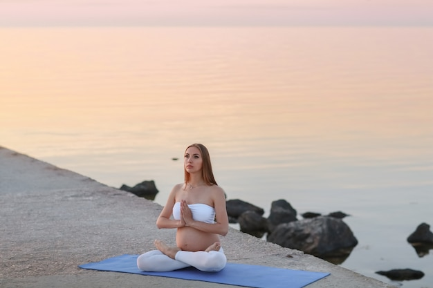 A woman sits in a yoga pose and meditates