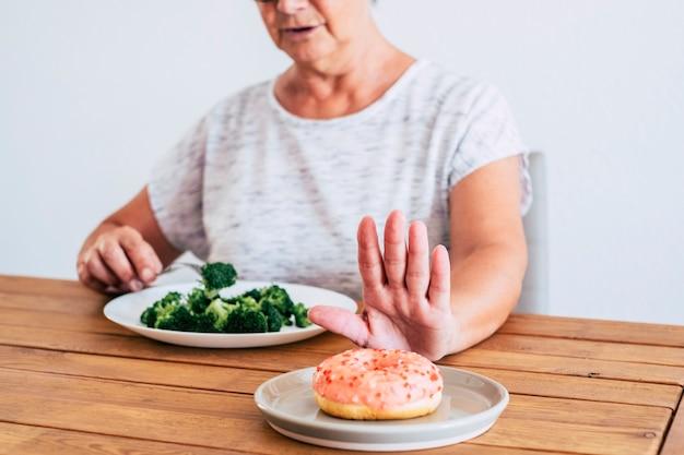 저녁 식사 때 나무 테이블에 앉아 도넛이 아닌 브로콜리를 선택하는 여성 - 건강하고 좋은 선택 - 다이어트 및 여성 노인 다이어트
