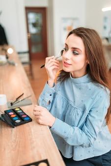 Женщина, сидящая против зеркала в студии красоты