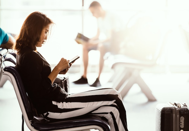 Woman sitting in airport lobby using smartphone and looking at screen while waiting for transit. sunlight shining from outside.