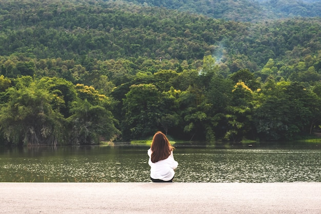 A woman sitting alone by the lake looking at the mountains with cloudy and green nature