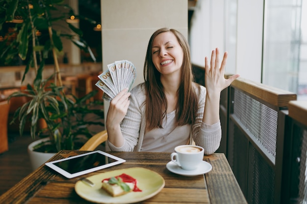 Woman sitting alone in coffee shop at table with bundle of dollars, cash money, cup of cappuccino, cake, relaxing in restaurant during free time. female working on pc tablet computer rest in cafe.