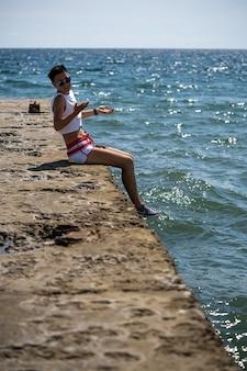 반바지와 신발을 신고 부두에 혼자 앉아 있는 여자. 뒷모습. 여름 바다