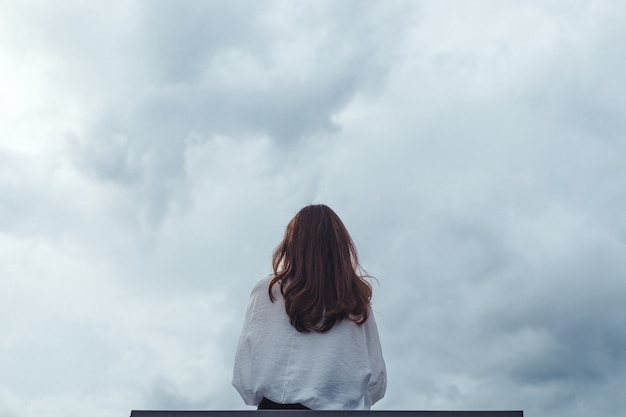 A woman sitting alone on a wooden bench in the park with cloudy and gloomy
