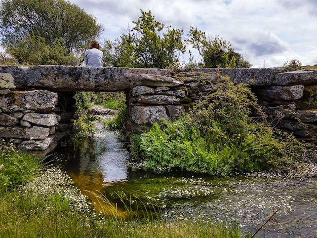 Woman sitting on ancient stone bridge above a stream of crystal clear water