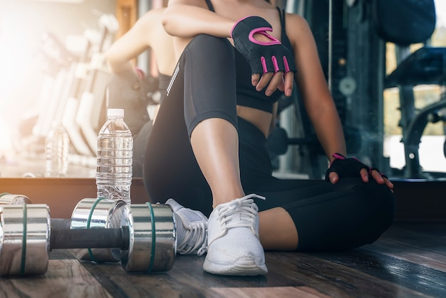 앉아서 체육관에서 운동 운동을하는 동안 휴식을 취하는 여자