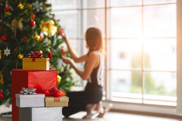 Женщина сидит и украшает елки в доме рядом с грудой подарочных коробок с теплым светом из стеклянного окна сзади.